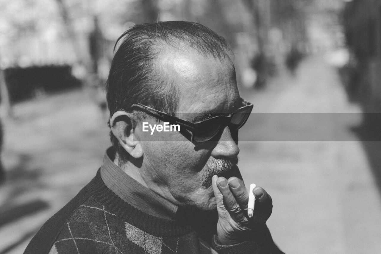 Close-Up Of Senior Man Smoking Cigarette Outdoors
