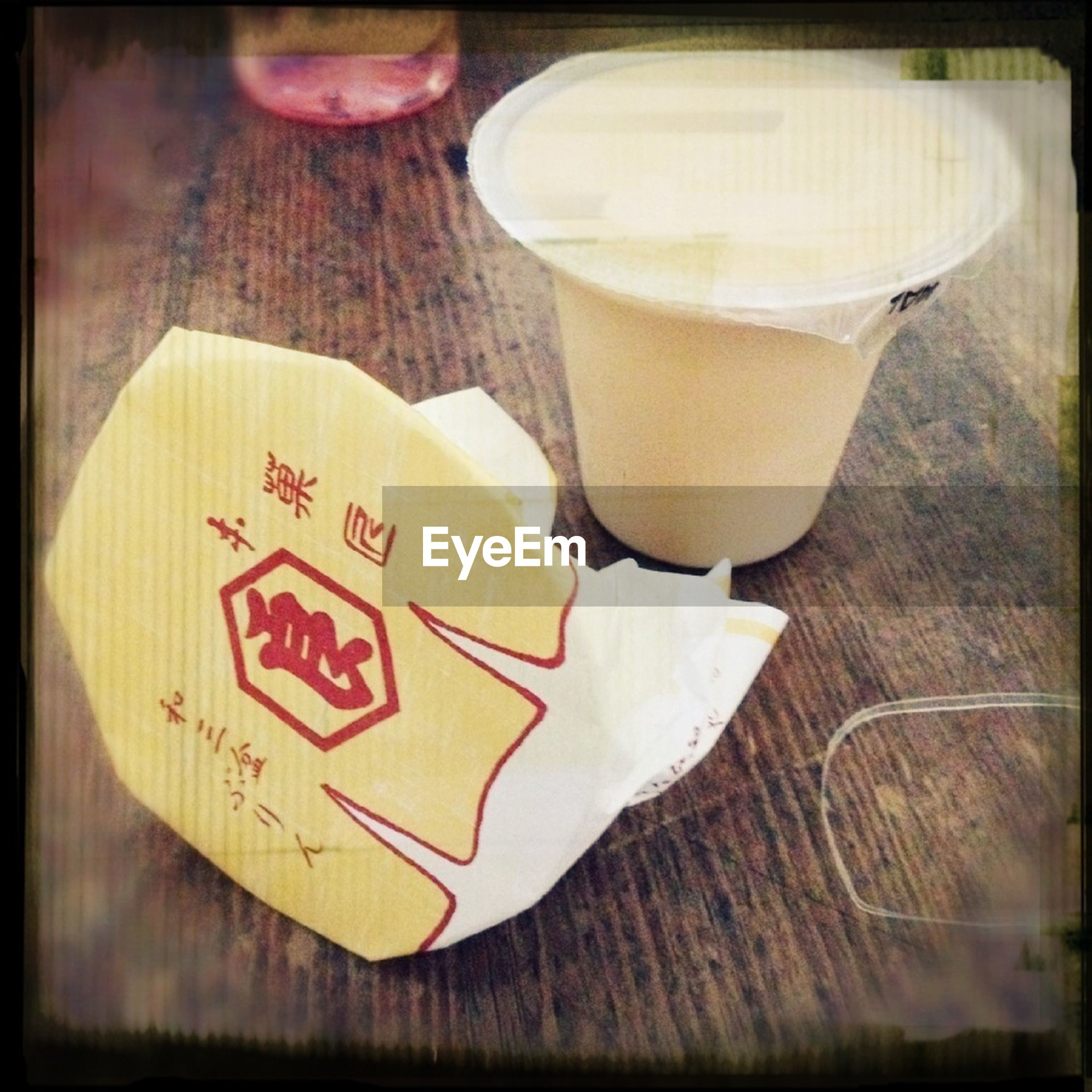 transfer print, text, western script, indoors, auto post production filter, communication, table, close-up, wood - material, still life, high angle view, heart shape, food and drink, one person, message, holding, paper, drink, non-western script, coffee cup