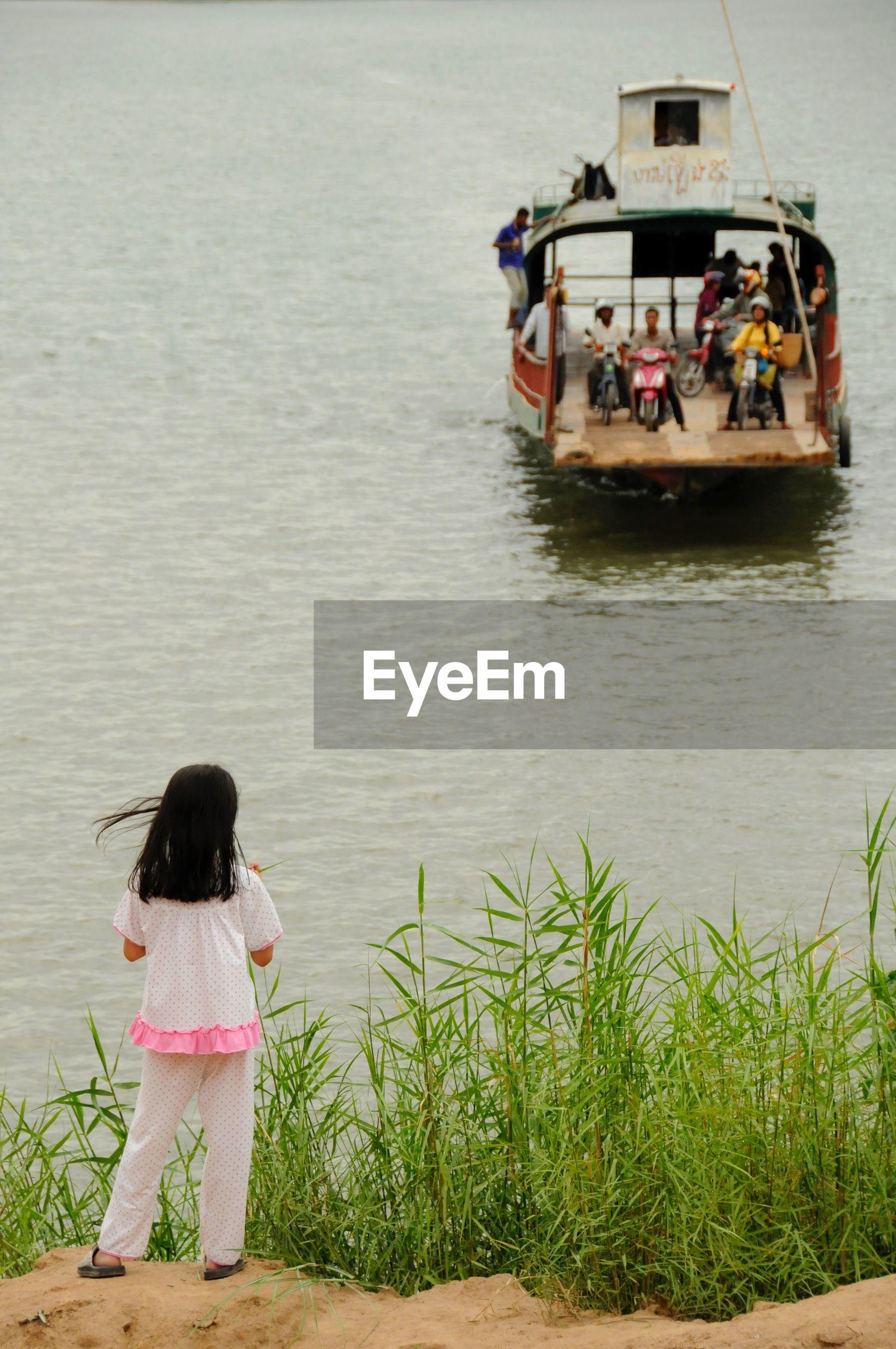 Rear view of girl looking at boat