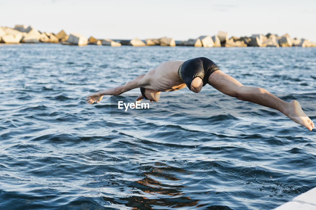 FULL LENGTH OF SENIOR MAN SURFING IN SEA