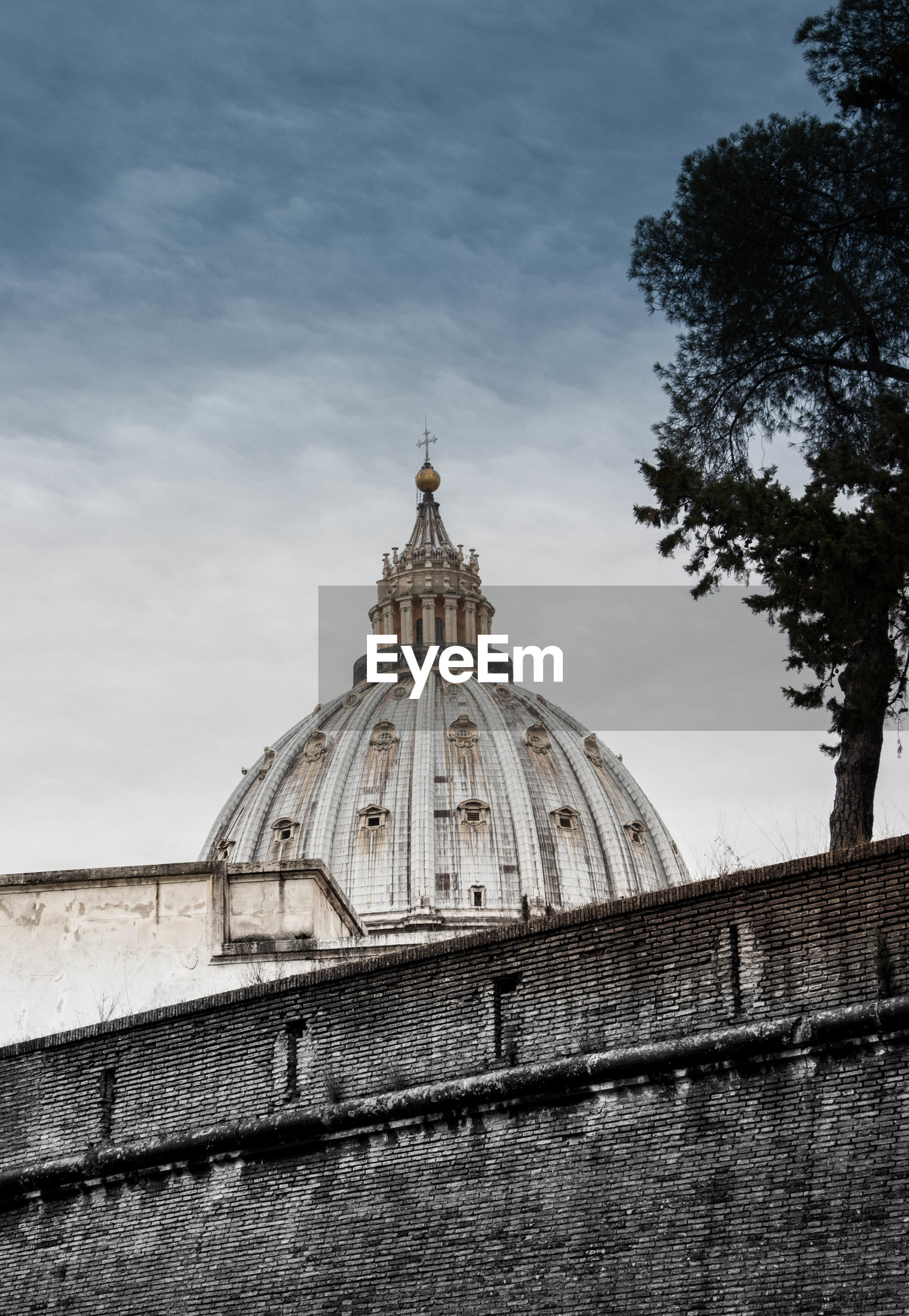 Low angle view of st peters basilica and buildings against cloudy sky