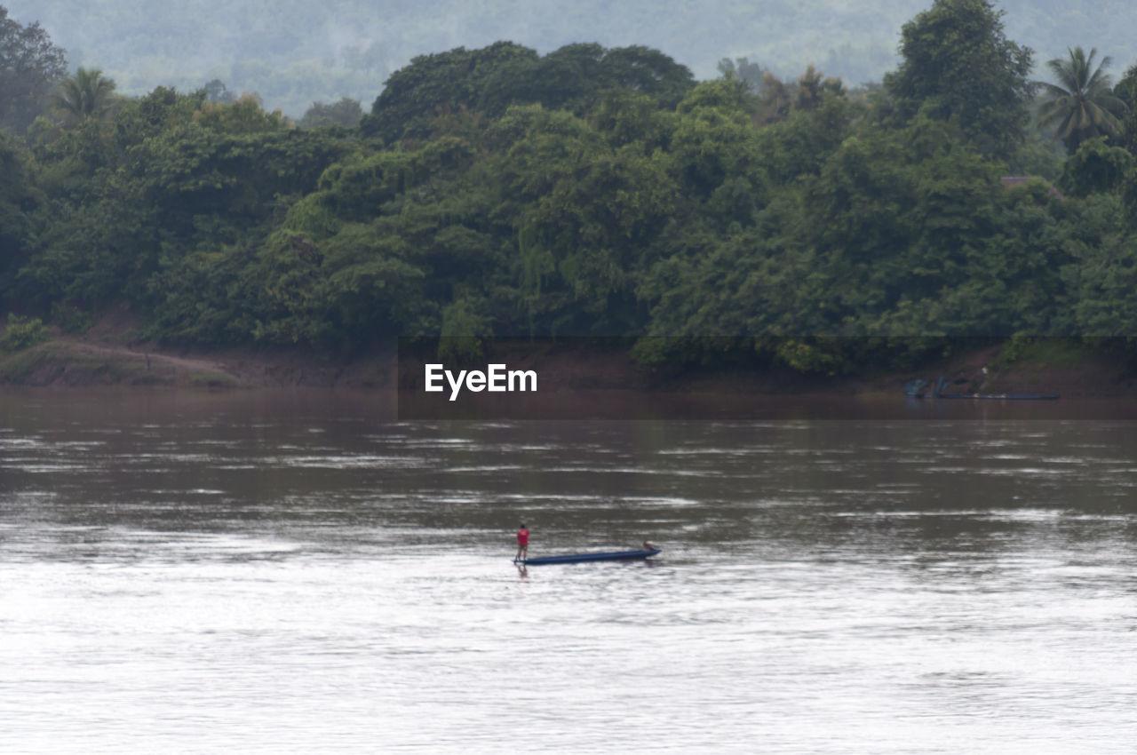 Fisherman On Boat In Lake Against Trees