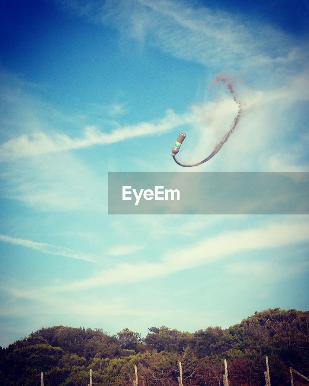 sky, mid-air, low angle view, flying, day, cloud - sky, motion, outdoors, nature, vapor trail, blue, no people, tree, airshow, beauty in nature