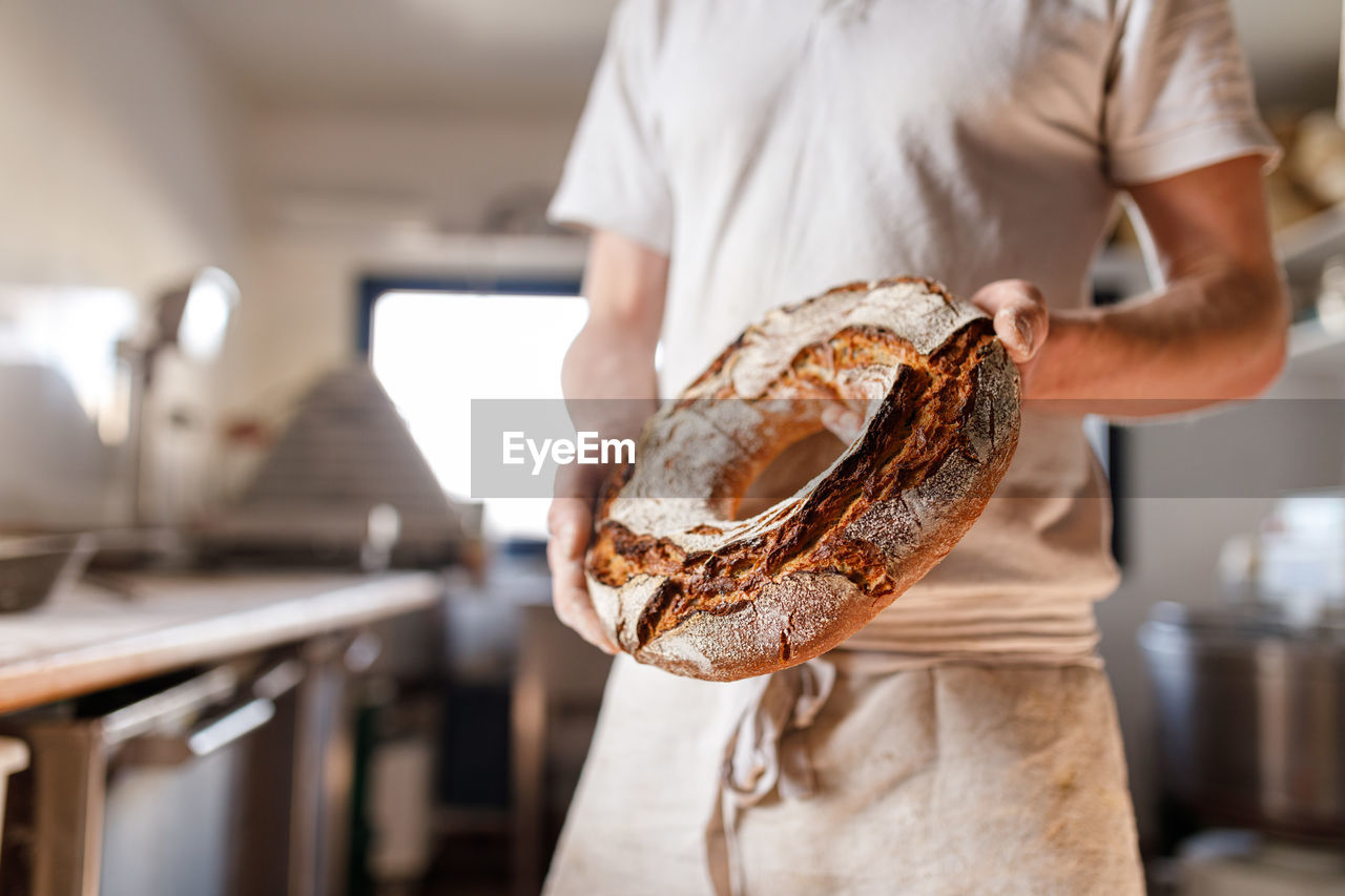 Midsection of baker holding round bread in bakery