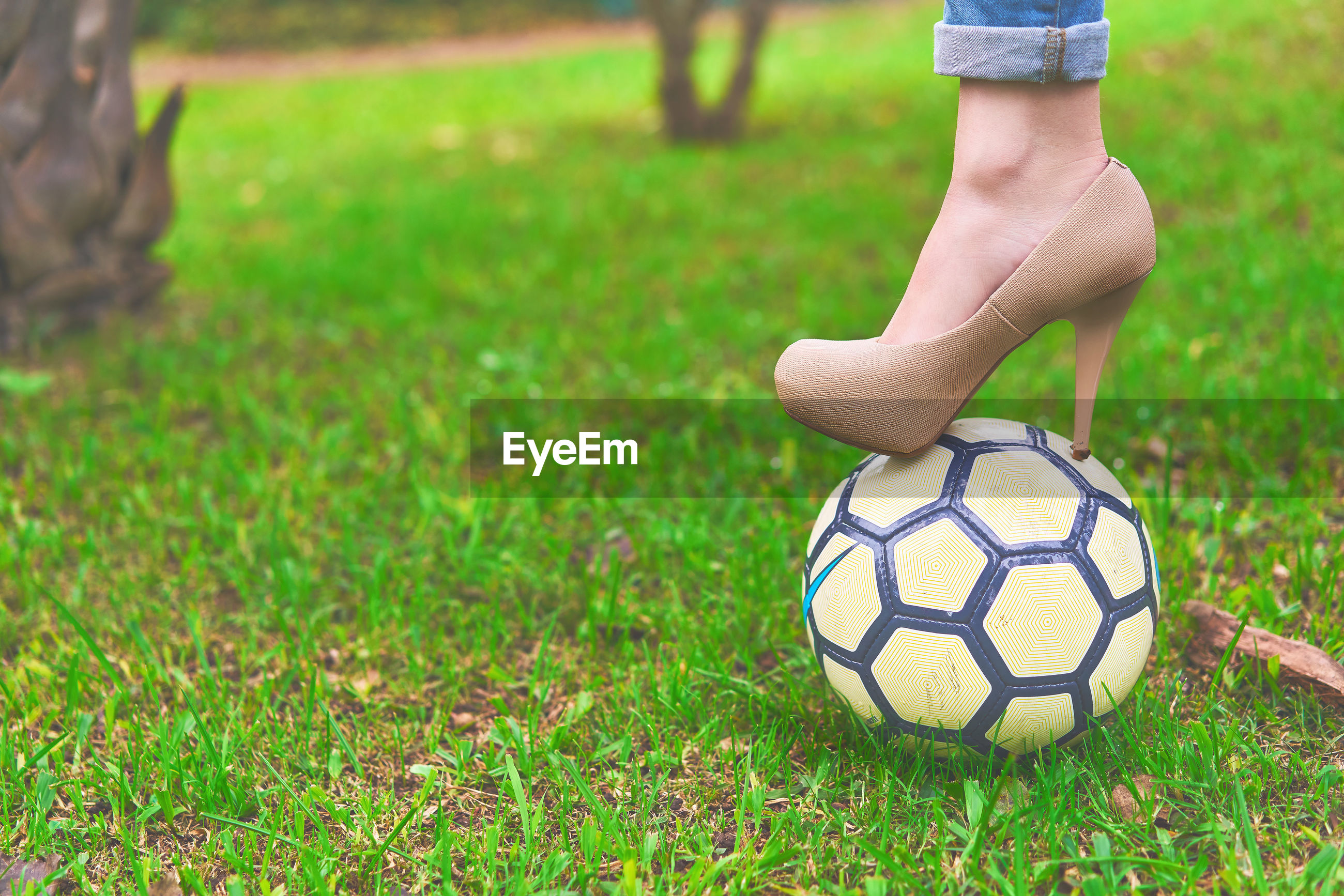Low section of woman standing on soccer ball over grassy field
