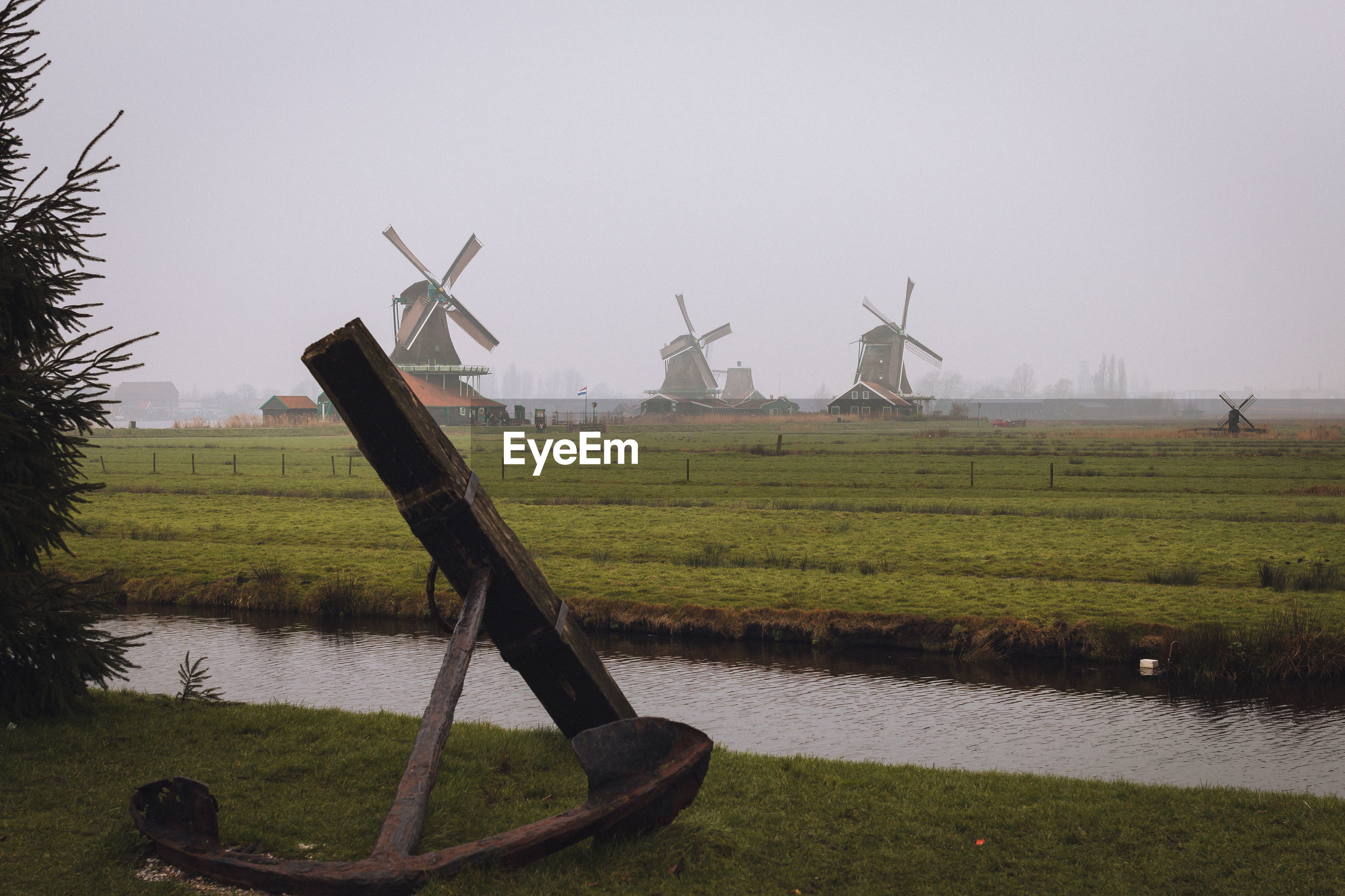 Stream amidst anchor and traditional windmills on field