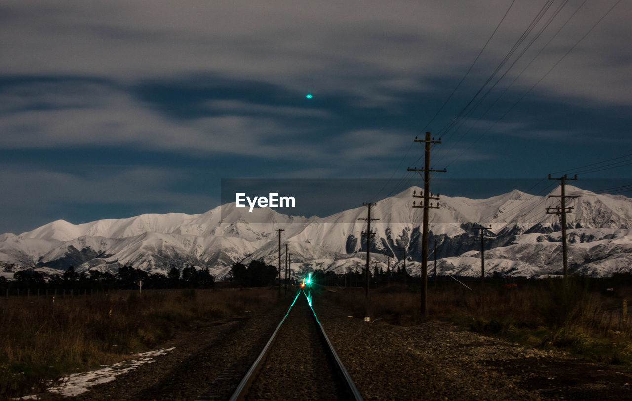 Diminishing Perspective Of Railroad Track Leading Towards Snowcapped Mountain Against Cloudy Sky At Night