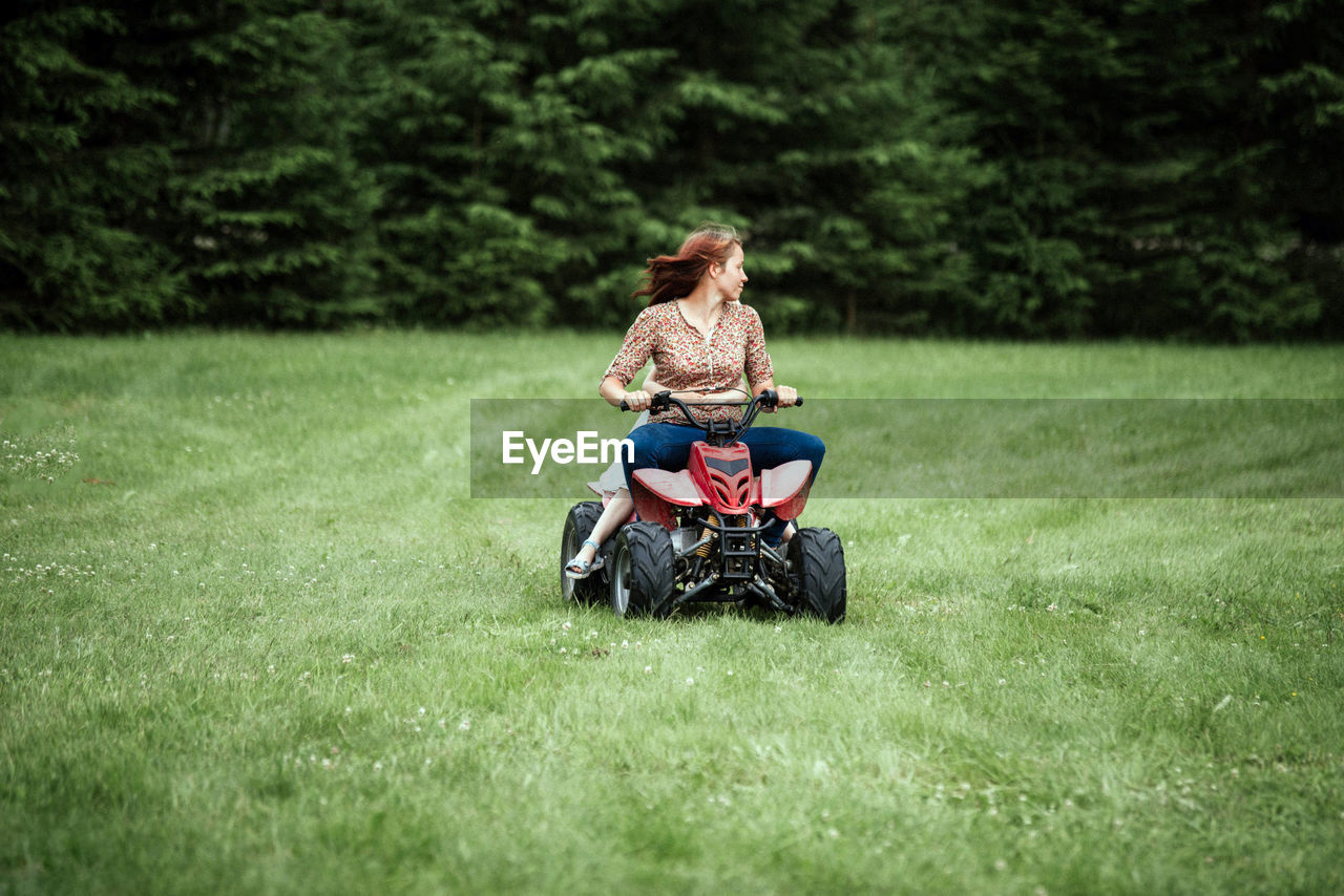Woman With Daughter Riding Race Car On Field