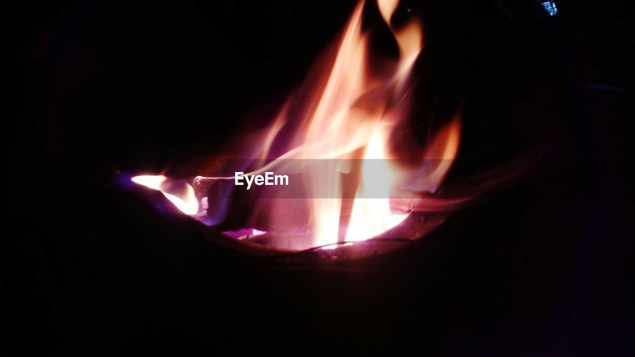 CLOSE-UP OF ILLUMINATED BURNING CANDLE