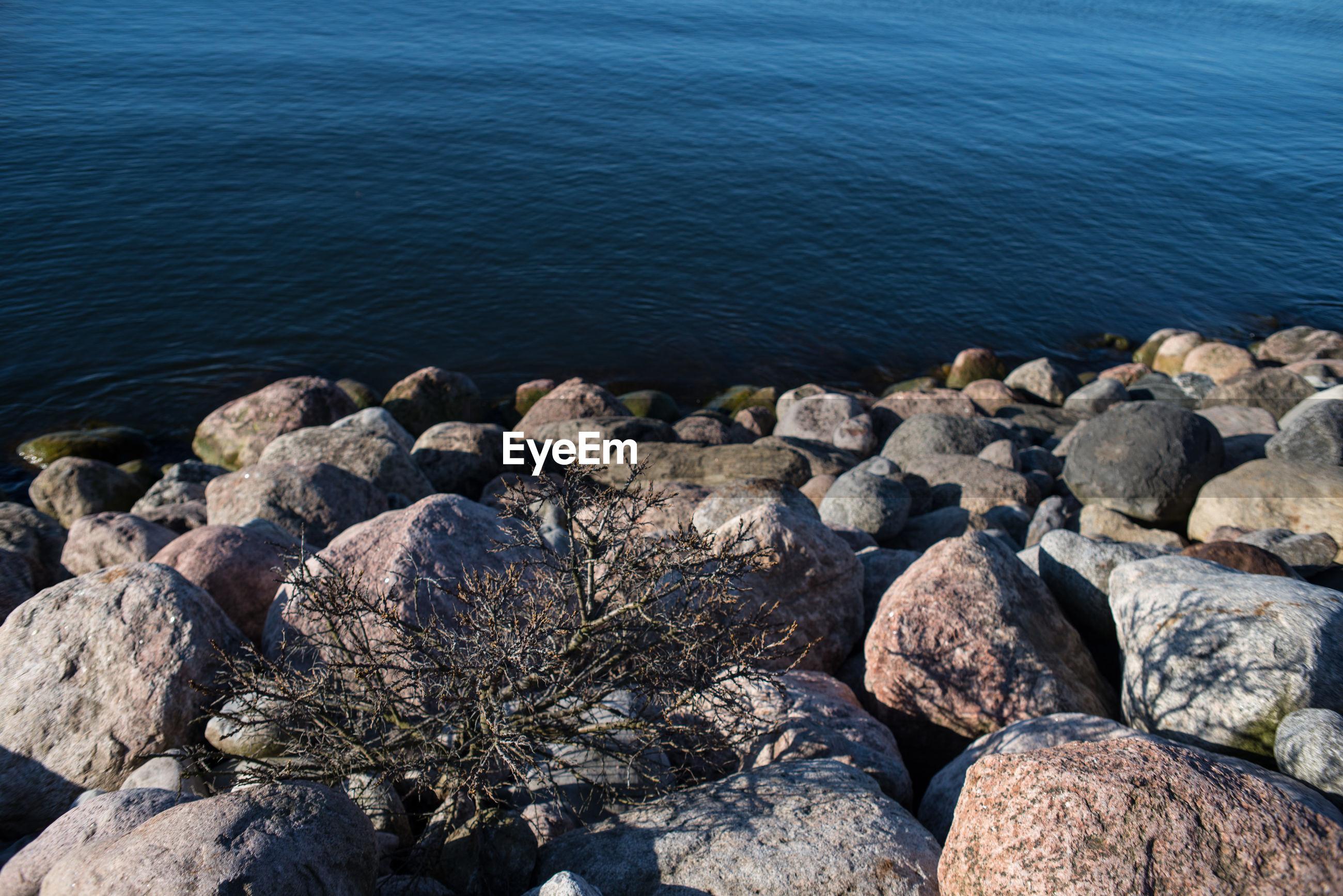 HIGH ANGLE VIEW OF PEBBLES AND SEA