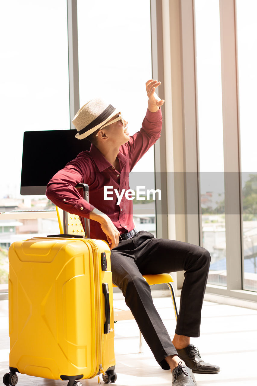 Man holding suitcase while sitting on chair against window