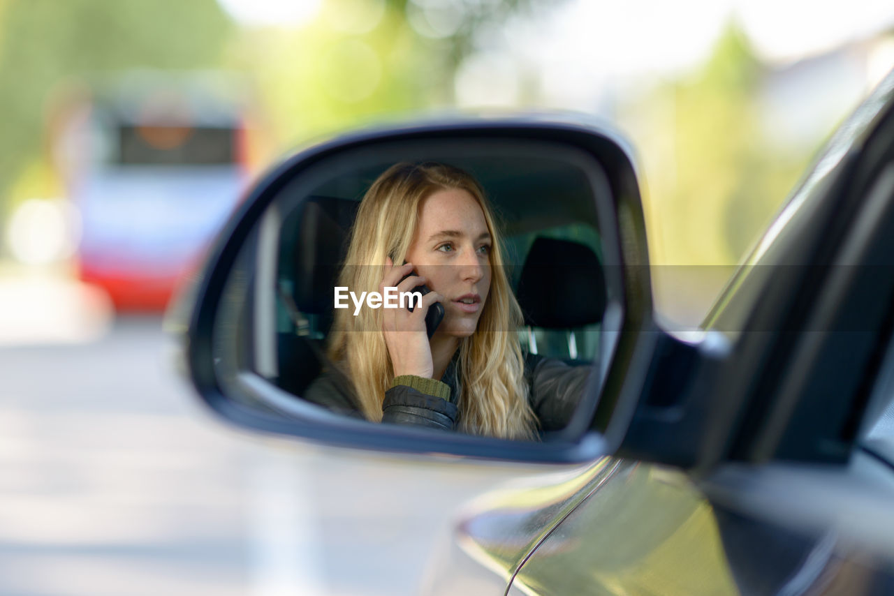 Young woman reflecting on car side-view mirror while talking on mobile phone