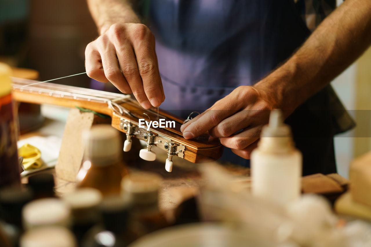 Midsection of man preparing guitar in workshop