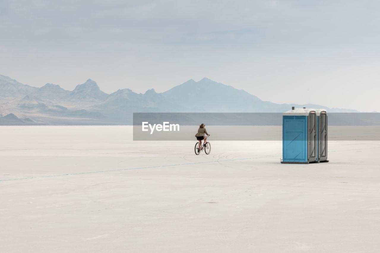 Woman Cycling On Salt Flat Against Sky