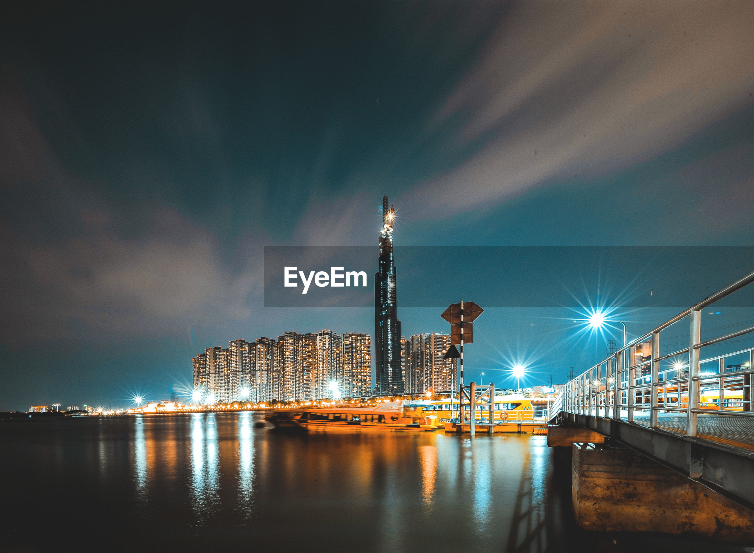 architecture, illuminated, water, built structure, sky, building exterior, night, city, transportation, cloud - sky, reflection, nature, river, waterfront, bridge - man made structure, bridge, no people, building, connection, tall - high, cityscape, skyscraper, office building exterior