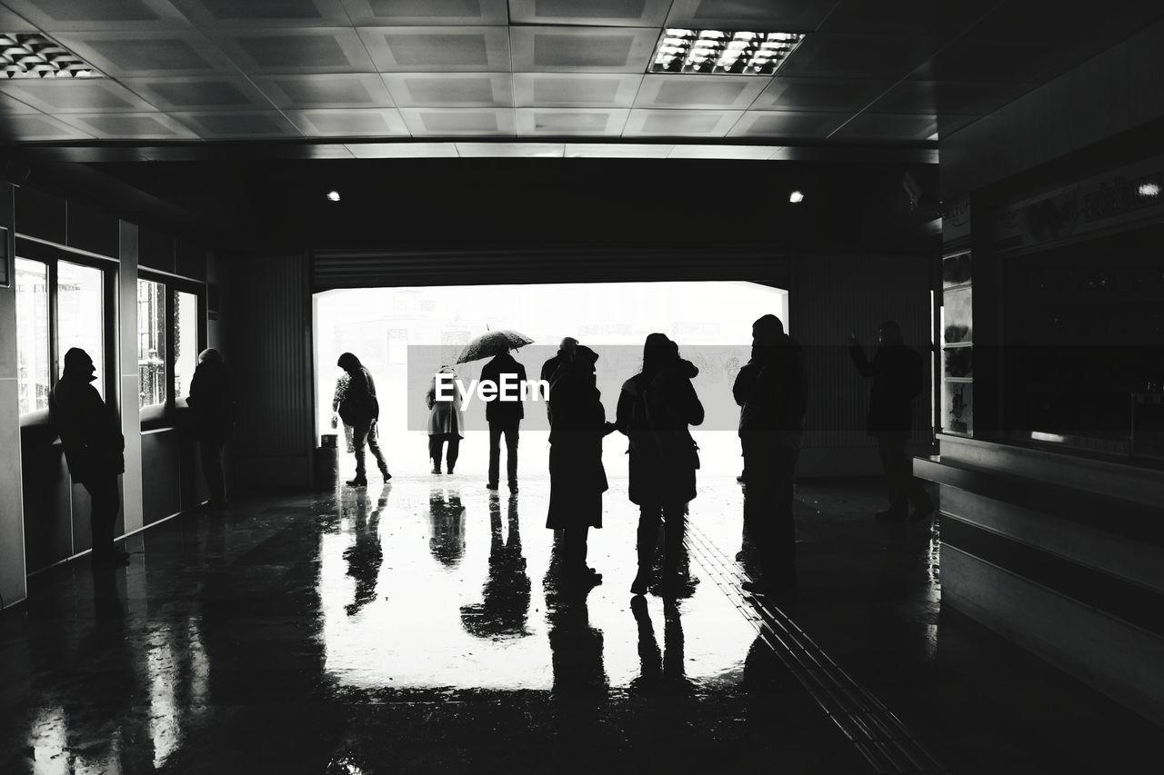 GROUP OF PEOPLE WALKING ON RAILWAY BRIDGE