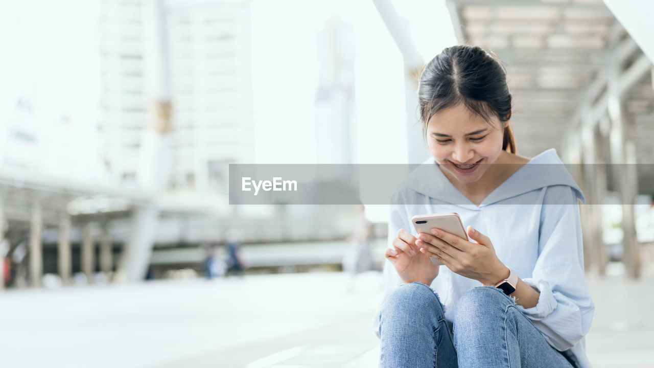 Smiling Young Woman Using Mobile Phone While Sitting In City