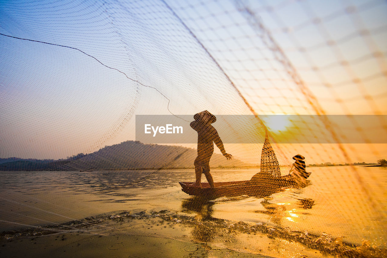 sky, water, sunset, real people, beach, full length, nature, beauty in nature, land, fishing, men, fishing net, sea, people, fisherman, lifestyles, scenics - nature, standing, outdoors, fishing industry