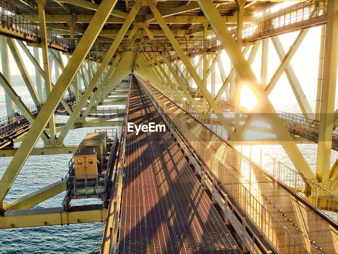 architecture, built structure, transportation, sunlight, bridge, connection, bridge - man made structure, water, no people, nature, metal, day, outdoors, travel, mode of transportation, low angle view, railing, sky, ceiling