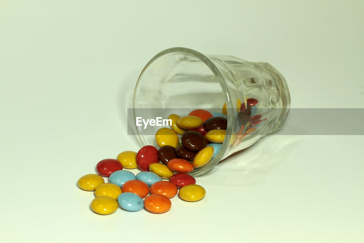 studio shot, white background, still life, indoors, large group of objects, sweet food, sweet, multi colored, no people, close-up, food and drink, healthcare and medicine, candy, food, medicine, pill, abundance, jar, spilling, cut out, temptation