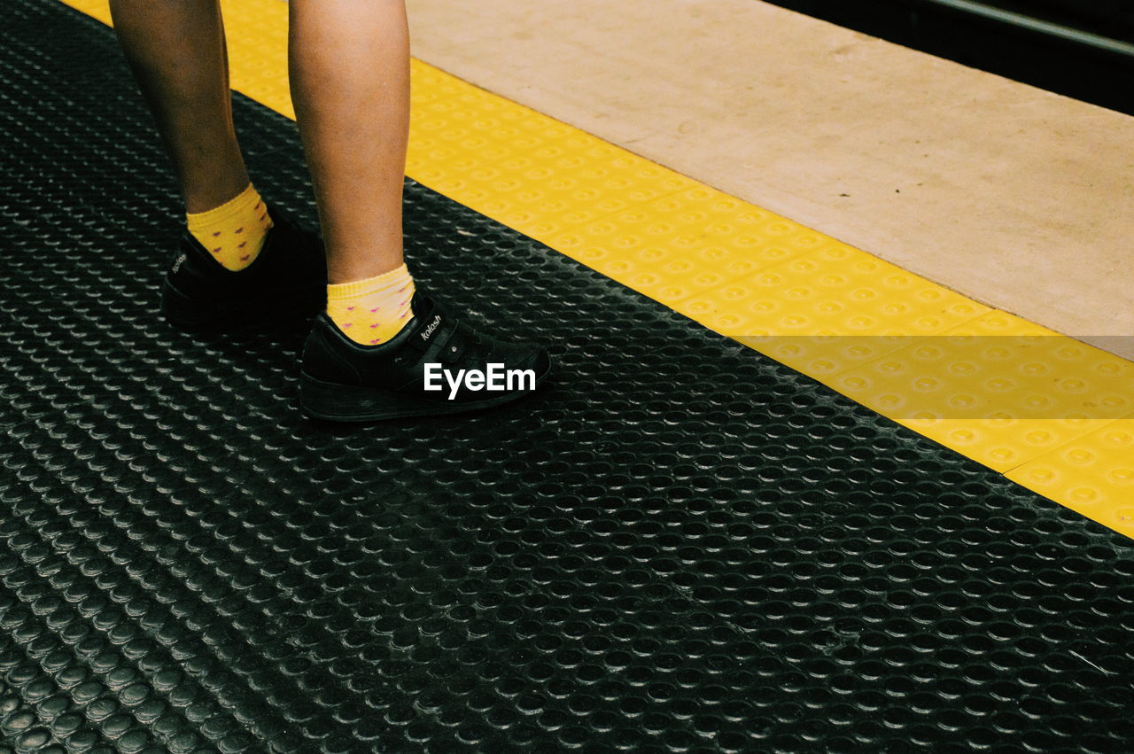 HIGH ANGLE VIEW OF WOMAN STANDING ON YELLOW FLOOR