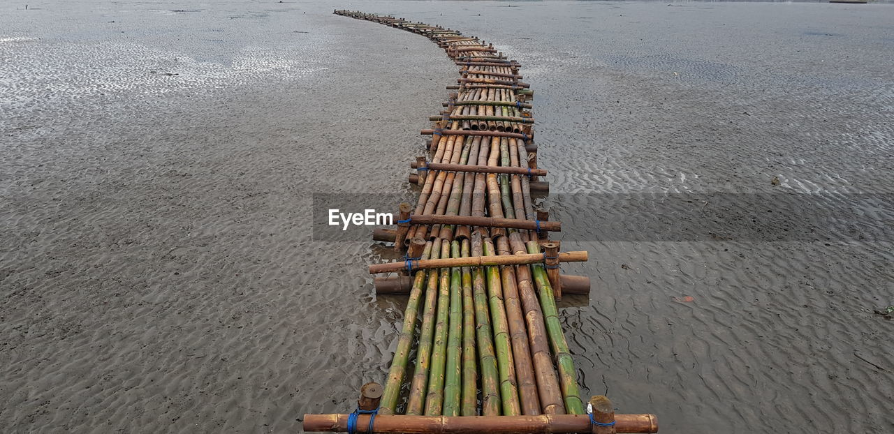 high angle view, day, water, no people, nature, beach, wood - material, outdoors, land, sand, architecture, bamboo - material, built structure, sea, transportation, large group of objects, in a row, road, nautical vessel