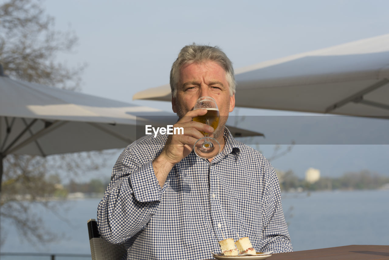 Portrait Of Senior Man Drinking Beer At Restaurant