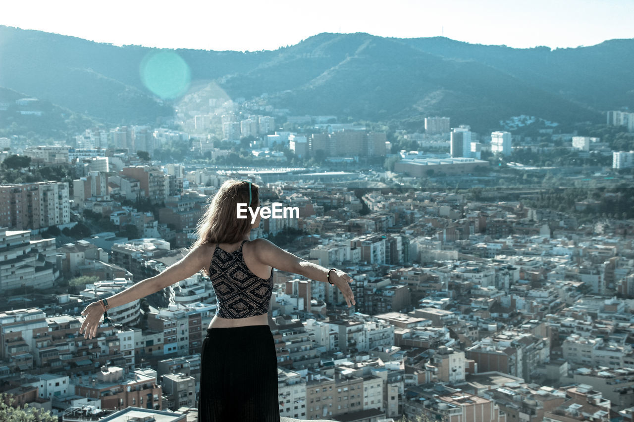 Woman Standing With Arms Outstretched By Cityscape And Mountains