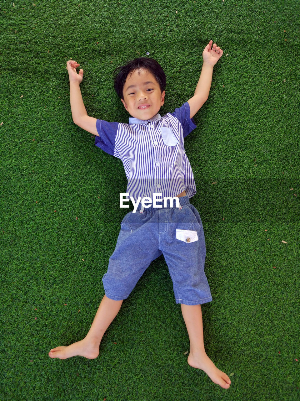 Directly above shot of boy lying on lawn