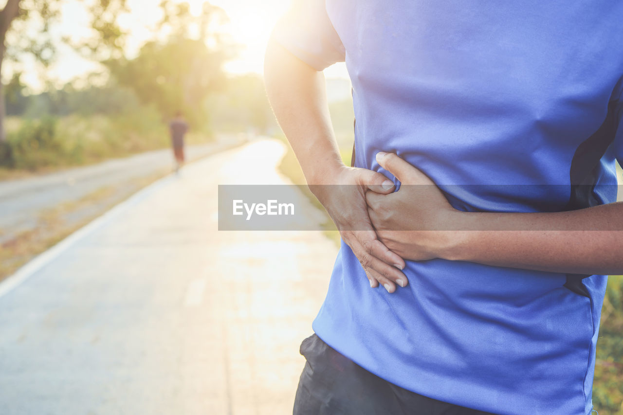 Midsection of man with stomachache standing on road