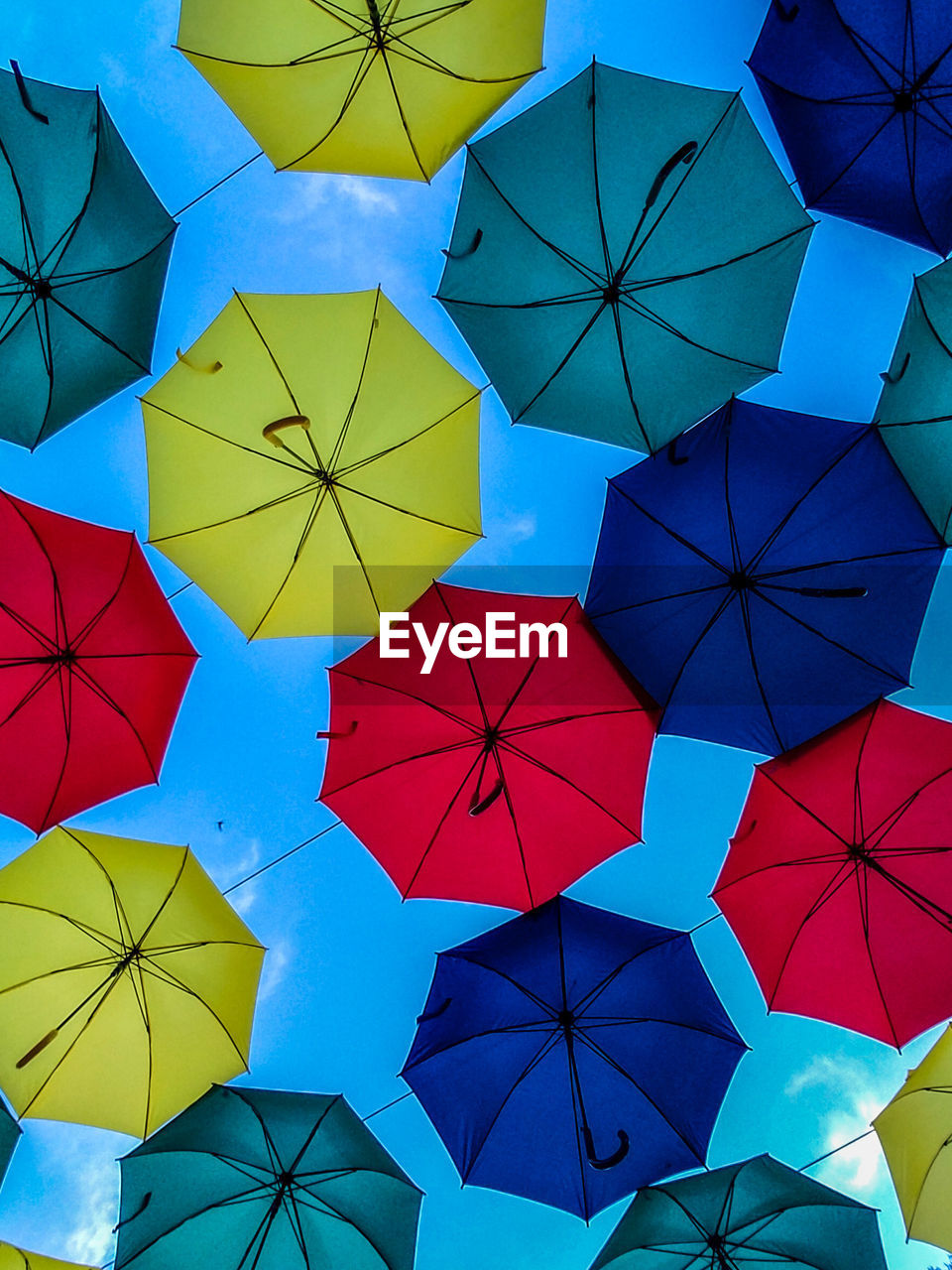 Low angle view of colorful umbrellas hanging against blue sky