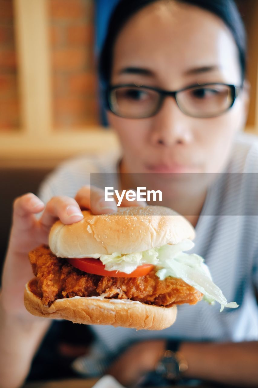 Young woman eating chicken burger