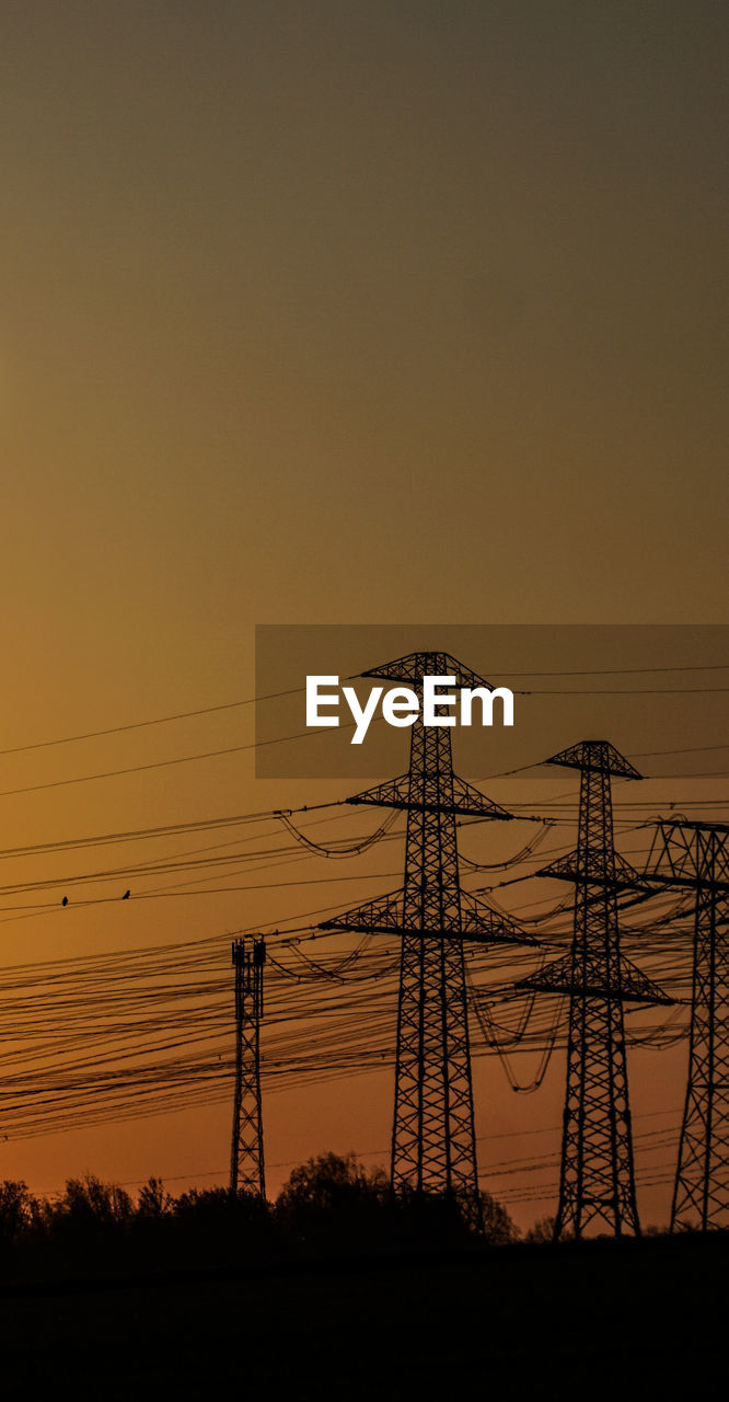 electricity, electricity pylon, cable, sky, technology, power line, sunset, power supply, fuel and power generation, connection, silhouette, nature, no people, low angle view, orange color, beauty in nature, copy space, outdoors, dusk, landscape, complexity