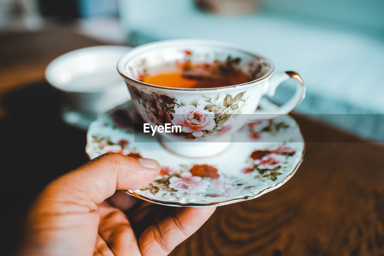 Close-Up Of Hand Holding Tea Cup Over Table