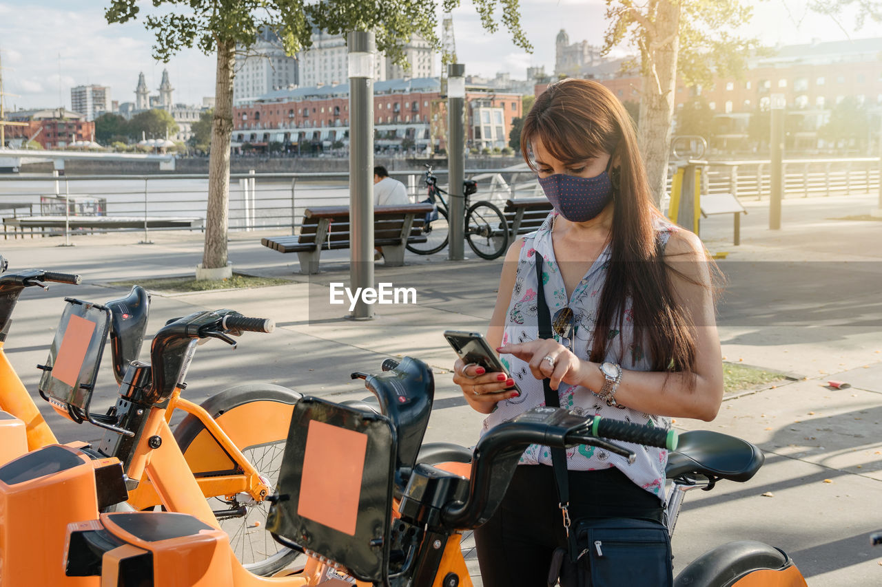 Woman using phone by bicycles in parking lot