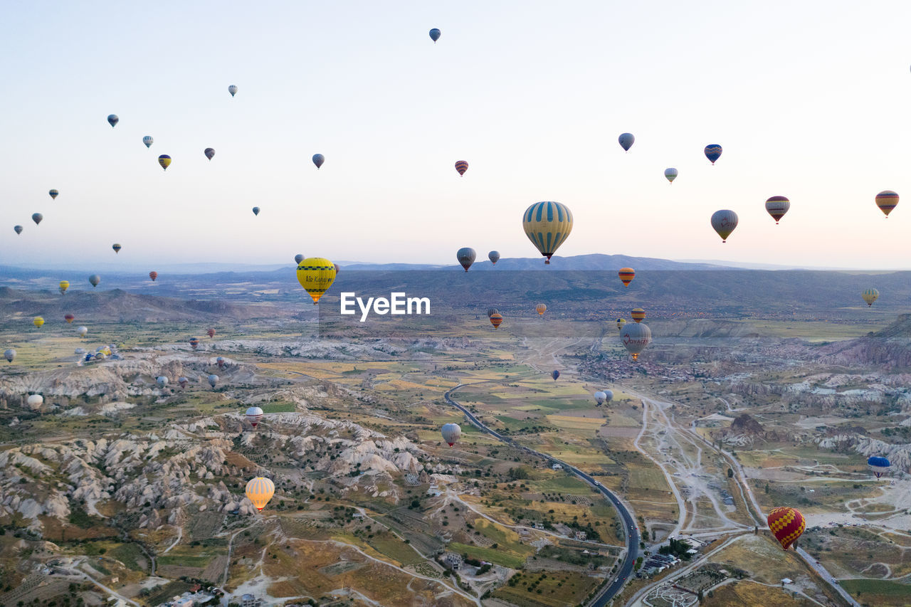 hot air balloon, air vehicle, balloon, mid-air, flying, environment, landscape, ballooning festival, sky, transportation, scenics - nature, mode of transportation, beauty in nature, nature, rock formation, non-urban scene, adventure, travel, mountain, no people, outdoors