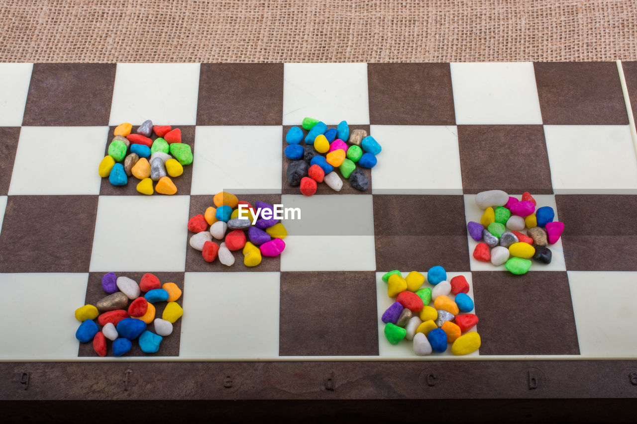 multi colored, large group of objects, indoors, leisure games, high angle view, no people, still life, game, candy, variation, board game, abundance, choice, strategy, close-up, shape, leisure activity, sweet food, directly above, sweet