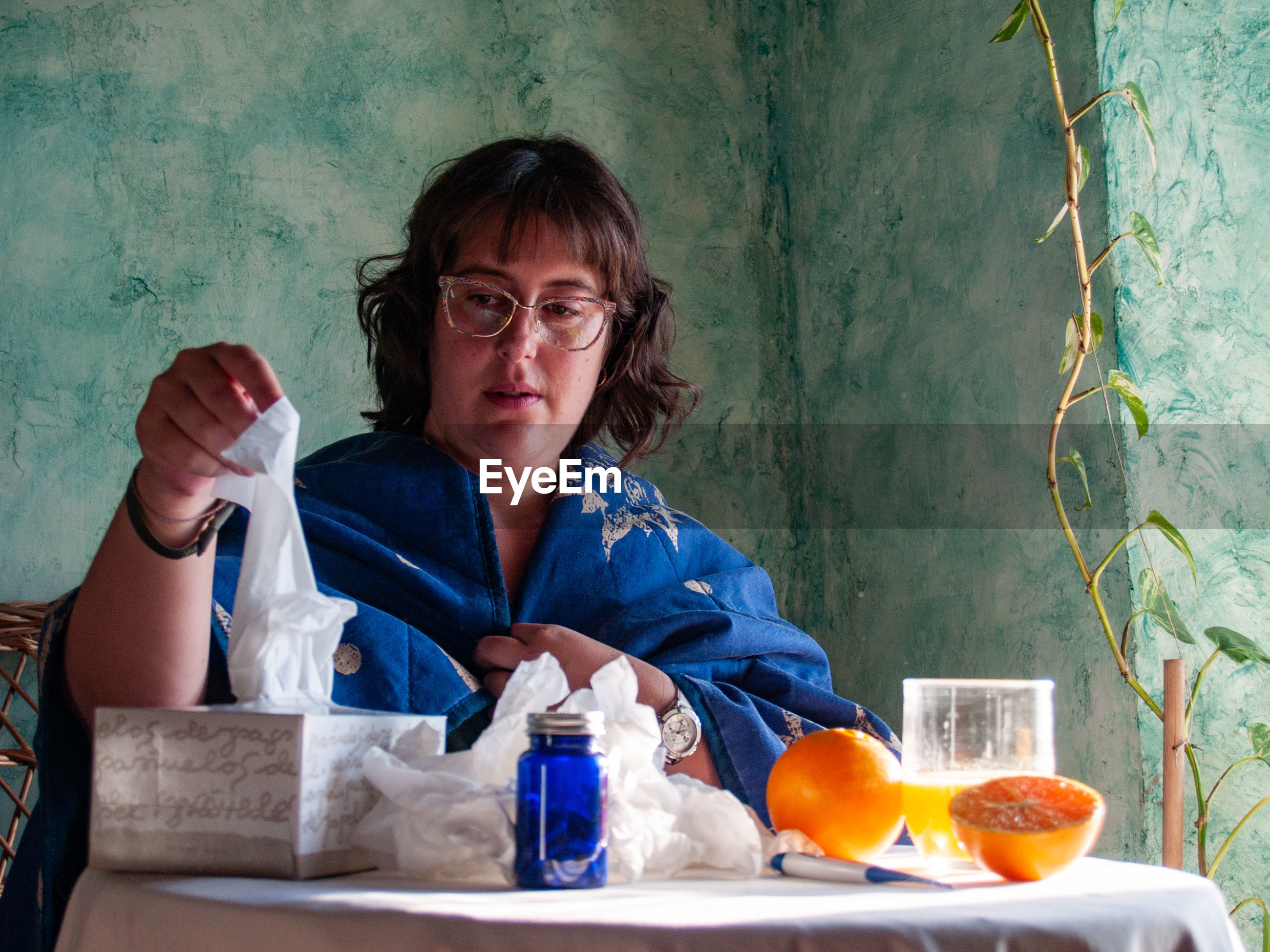 Woman holding tissue paper by oranges on table at home