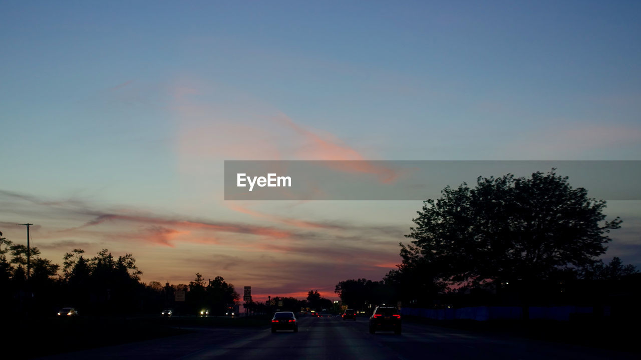 sky, tree, motor vehicle, transportation, plant, sunset, car, cloud - sky, mode of transportation, land vehicle, nature, road, no people, silhouette, beauty in nature, street, city, orange color, architecture, dusk, outdoors