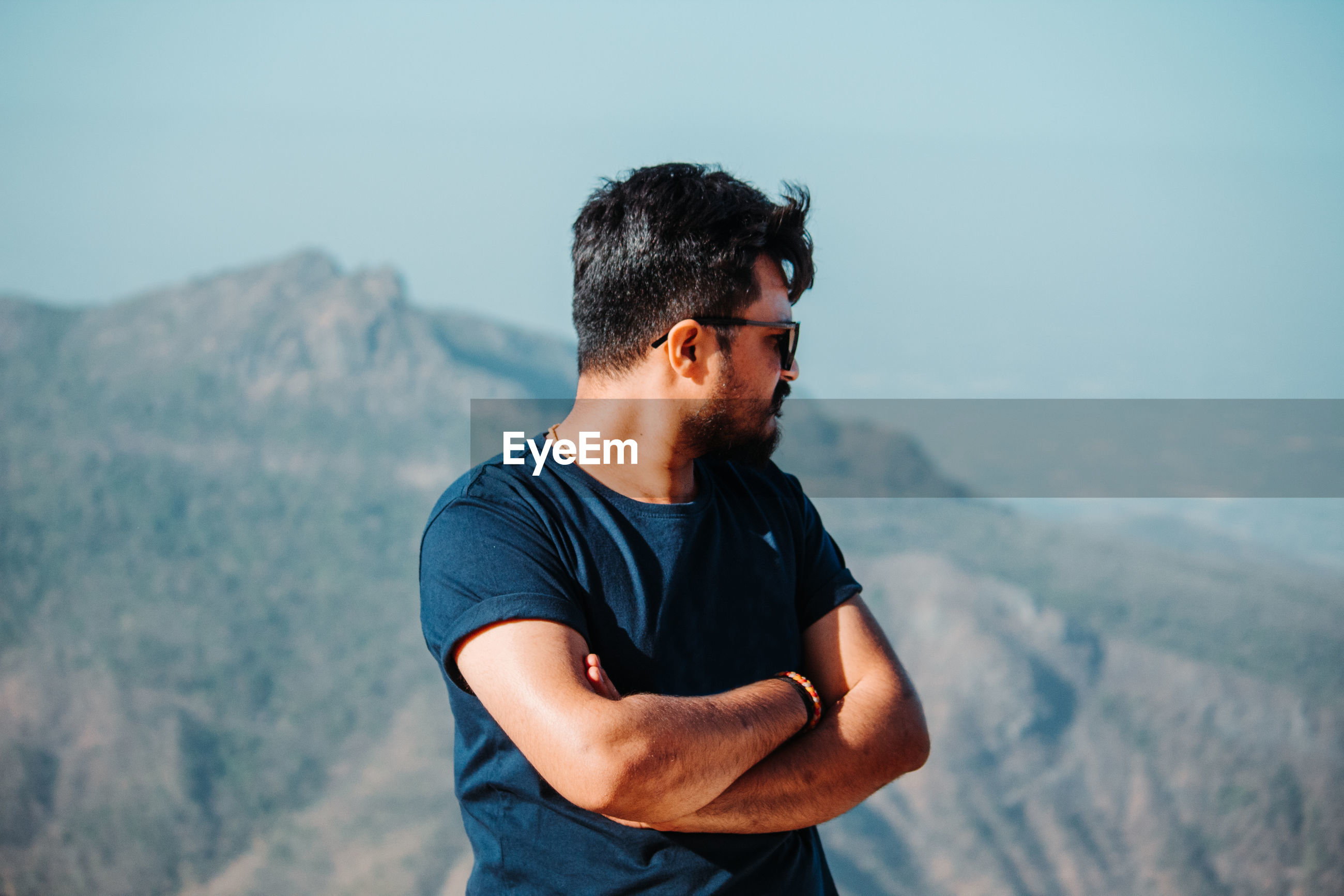YOUNG MAN WEARING SUNGLASSES STANDING BY MOUNTAIN