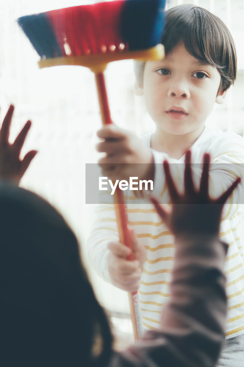 Cute boy holding broom while looking away at home