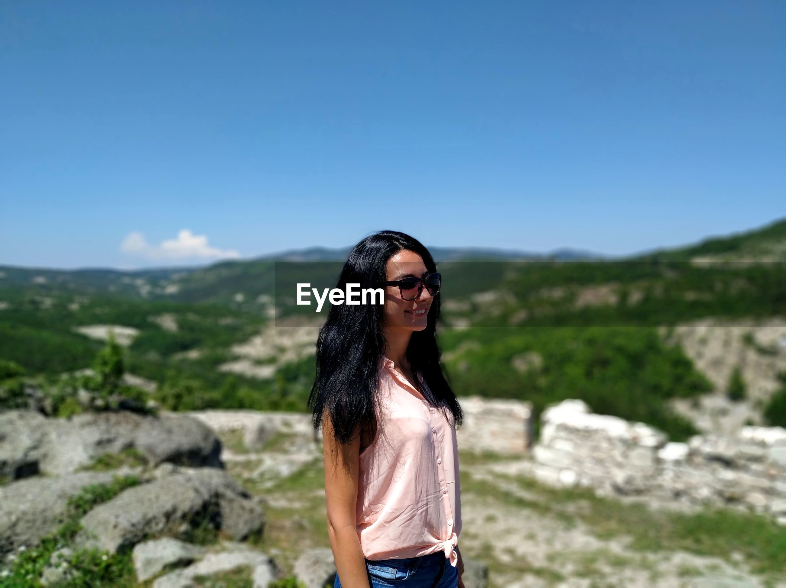 Portrait of young woman wearing sunglasses standing on mountain against sky