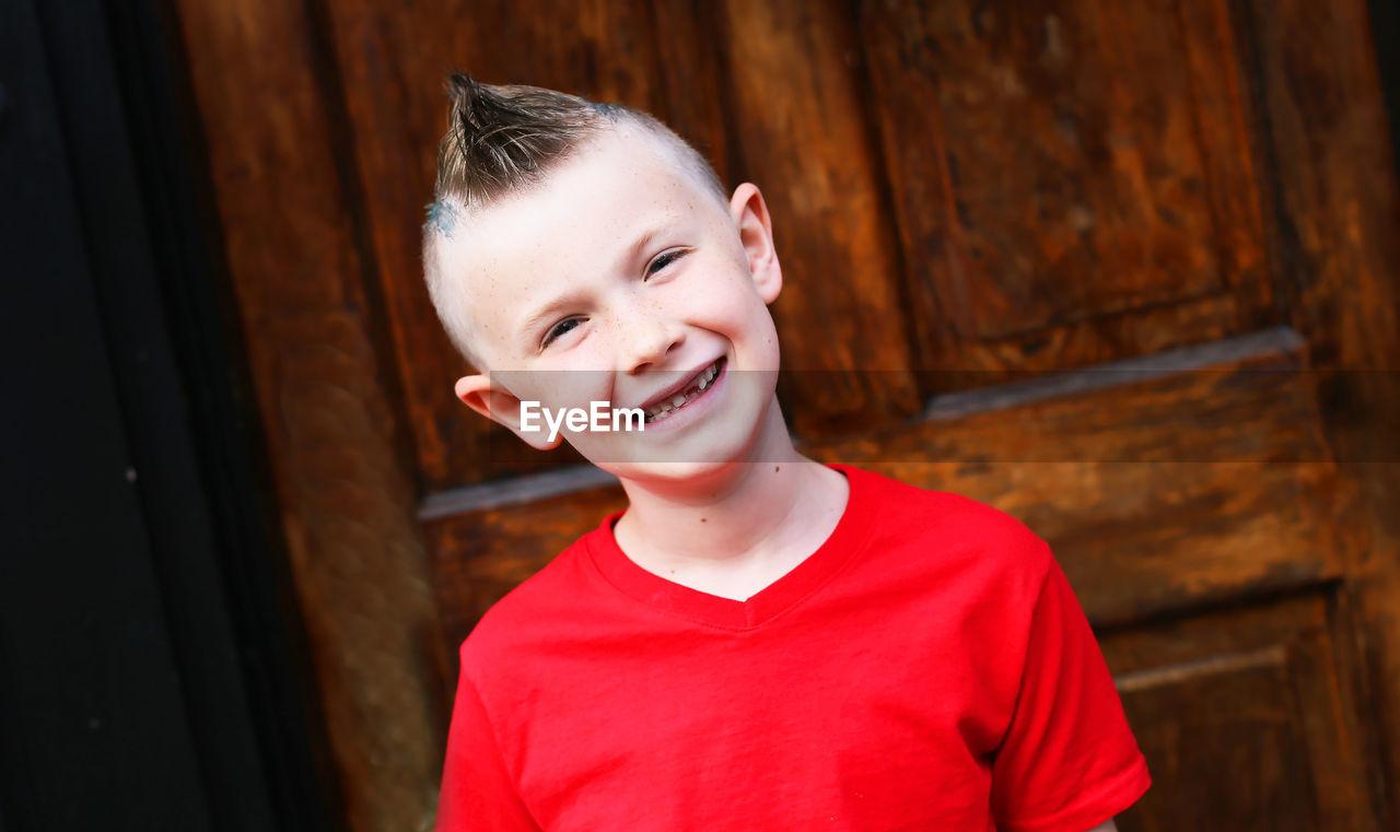 Portrait of smiling boy standing against door