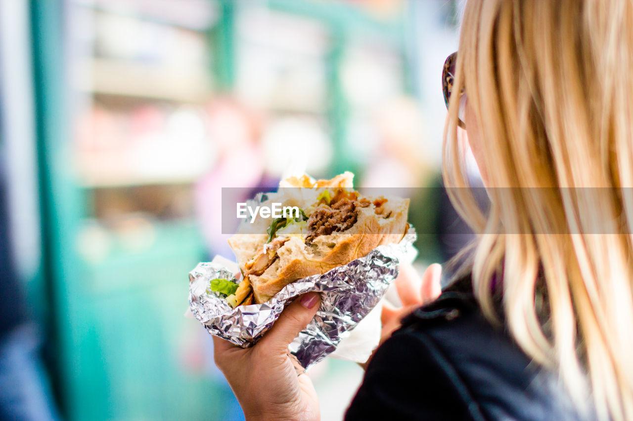 Cropped Image Of Woman Holding Hamburger