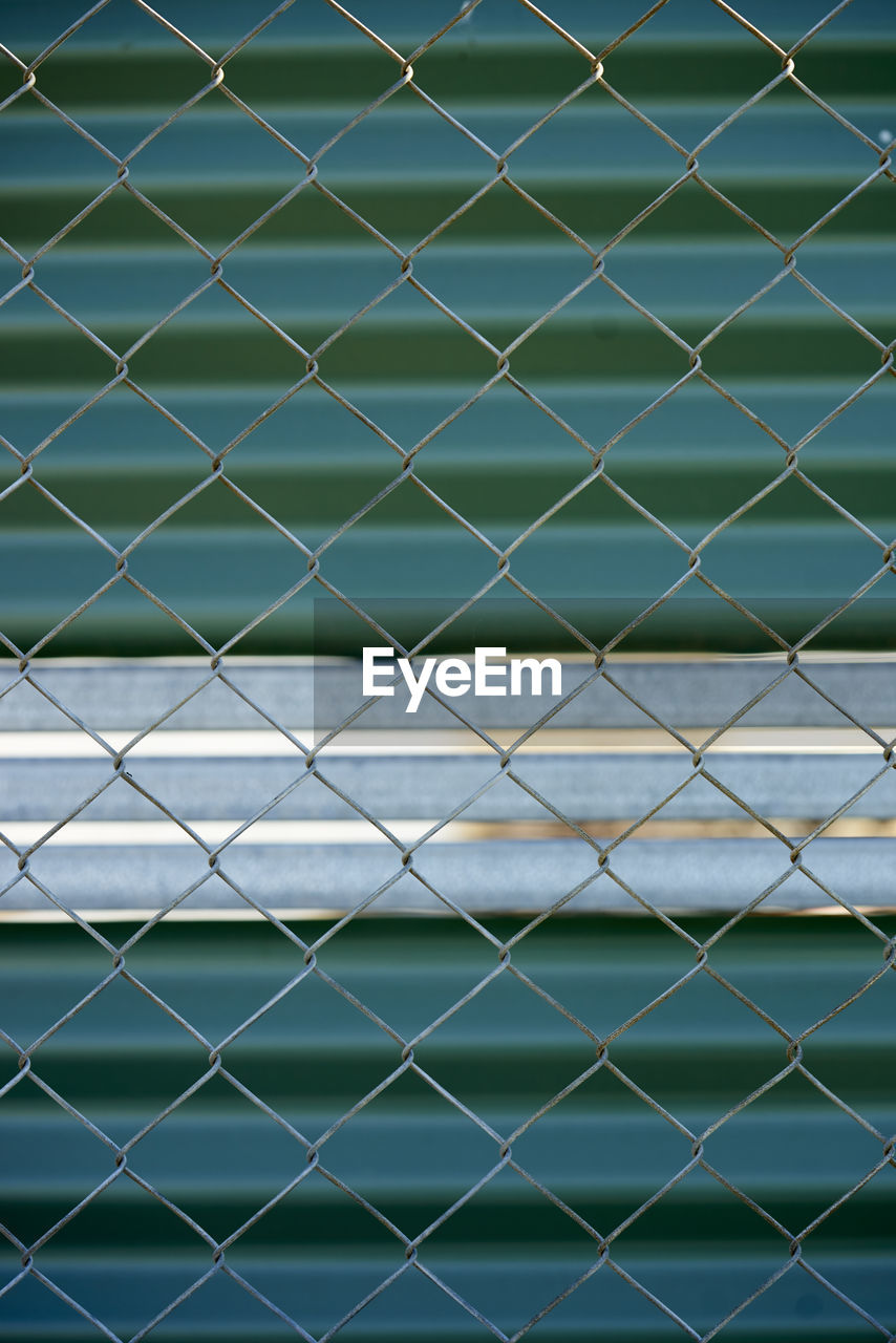 Full Frame Shot Of Chainlink Fence Against Shutter