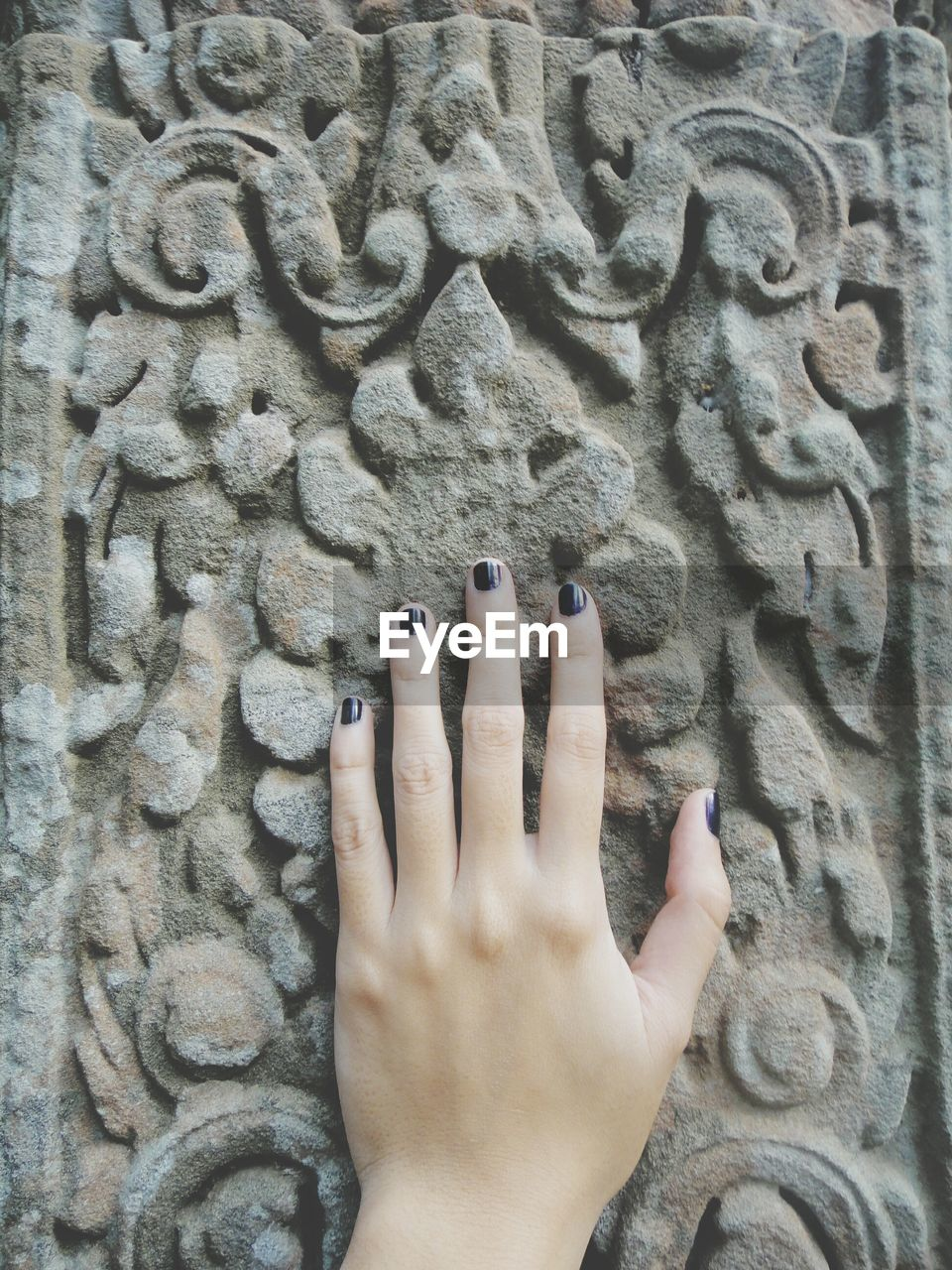 Cropped Hand Of Woman Touching Carved Wall