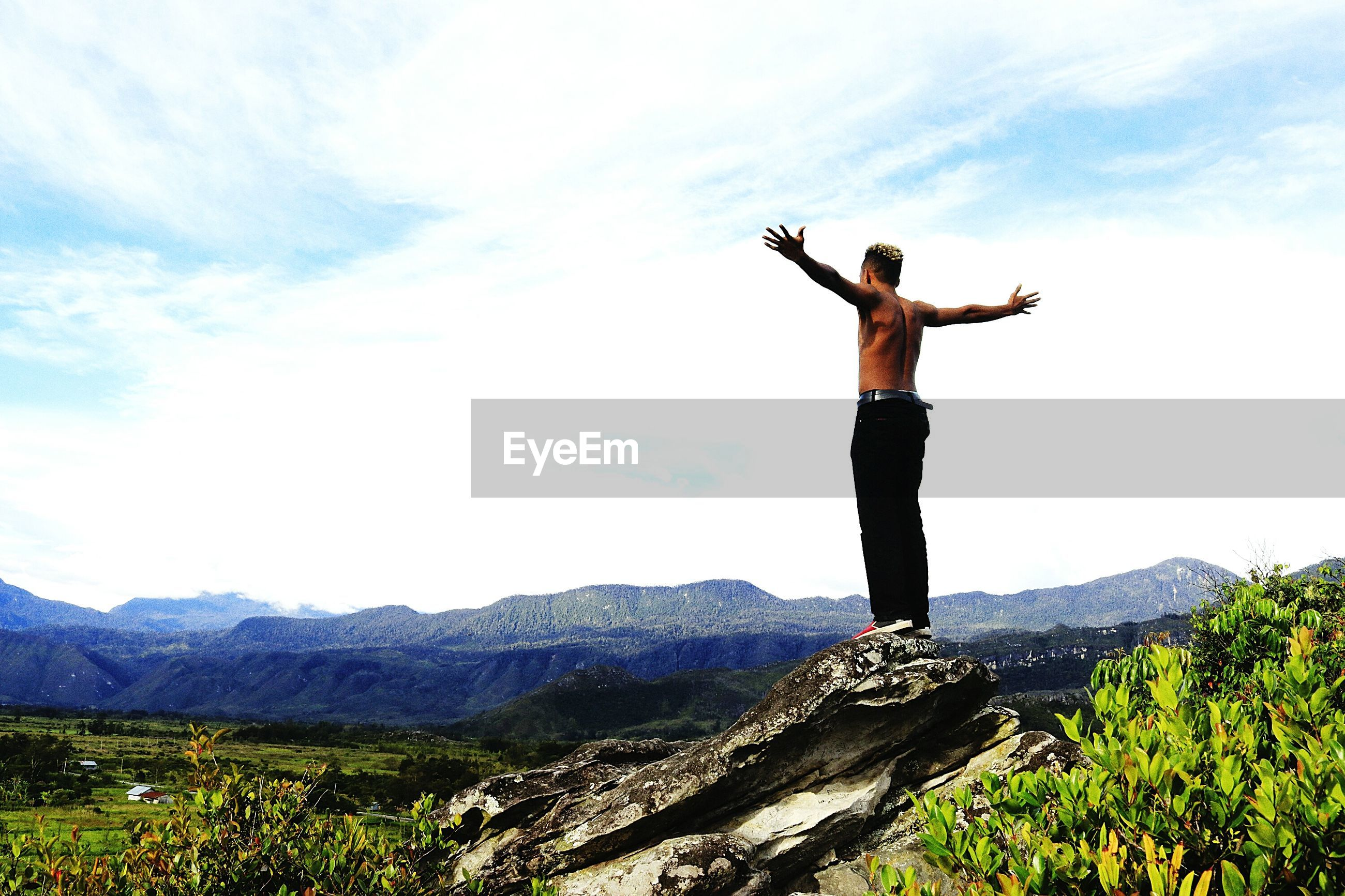 Low angle view of shirtless young man with arms outstretched standing on mountain against cloudy sky