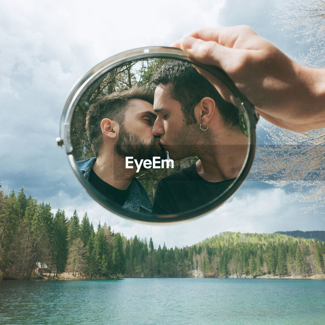 Reflection Of Lesbian Couple Kissing In Mirror Held By Hand Over Lake Against Sky