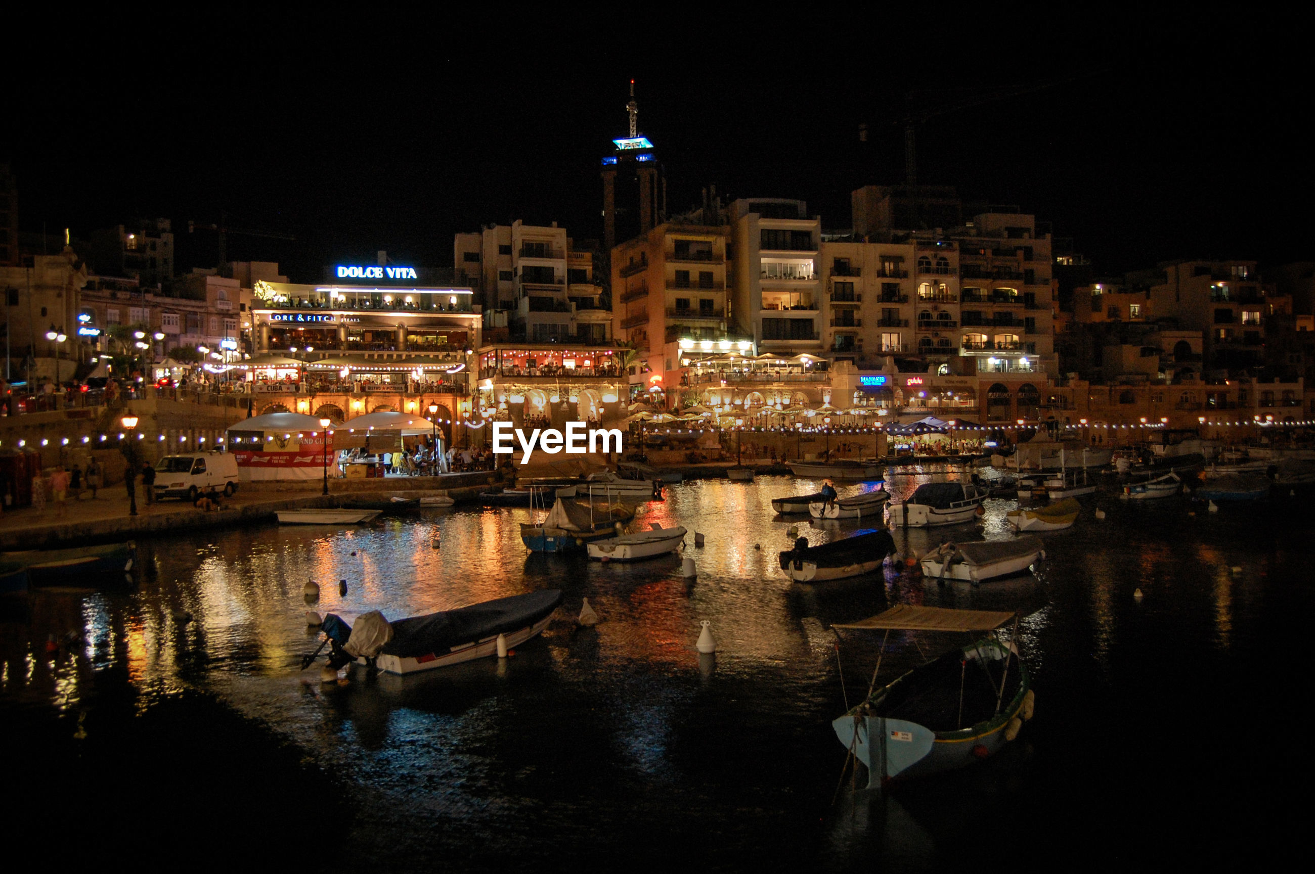 BOATS MOORED AT HARBOR AGAINST BUILDINGS AT NIGHT