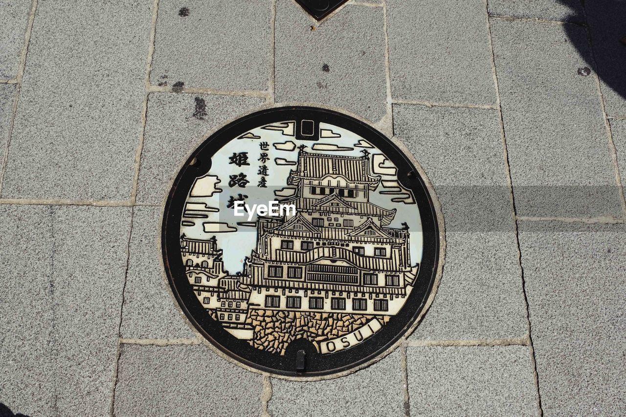 circle, geometric shape, shape, street, day, footpath, no people, text, stone, manhole, paving stone, high angle view, city, outdoors, western script, close-up, metal, communication, sidewalk, transportation